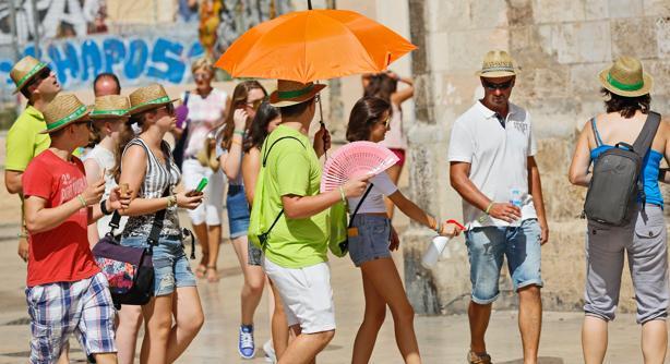Un grupo de personas se protege el intenso calor en Valencia
