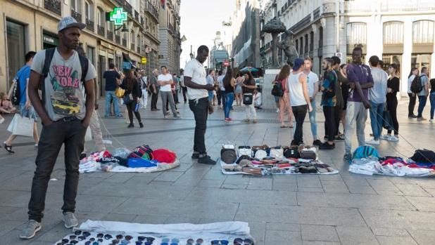 Varios manteros despliegan su muestrario en la Puerta del Sol