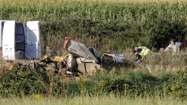 Dos guardias civiles investigan los restos de la avioneta que esta tarde se ha estrellado en una finca situada en las proximidades del Villanueva del Condado (León)