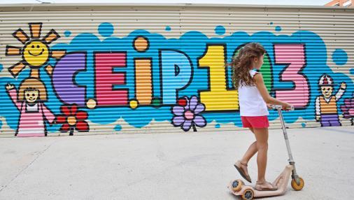 Un niña juega delante de uno de los barracones del Ceip 103