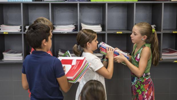 Varios alumnos organizan el material escolar en el marco del programa XaxaLlibres