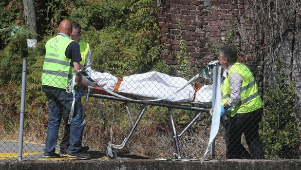 Los operarios trasladan a una de las víctimas del accidente de tren de O Porriño