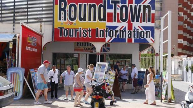 Traseúntes en una oficina de información para turistas británicos en Benidorm