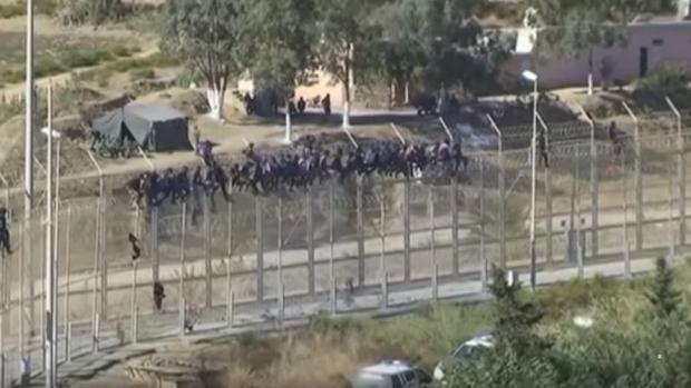 Imagen de los inmigrantes que este sábado se han encaramado a la valla de Ceuta