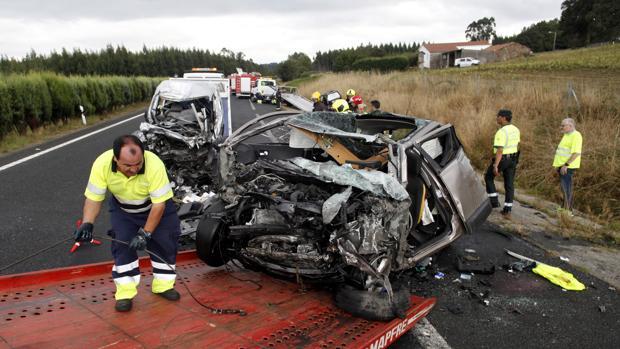 Un operario retira uno de los vehículos siniestrado en un accidente en la A-6 que comunica A Coruña con Guitiriz (Lugo)