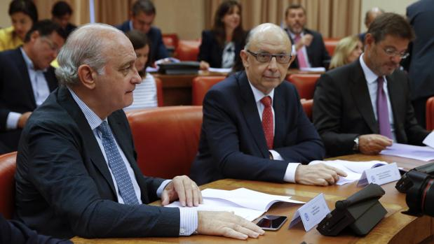 De Guindos (a la izquierda) y Catalá (a la derecha), durante la reunión de este lunes en el Congreso