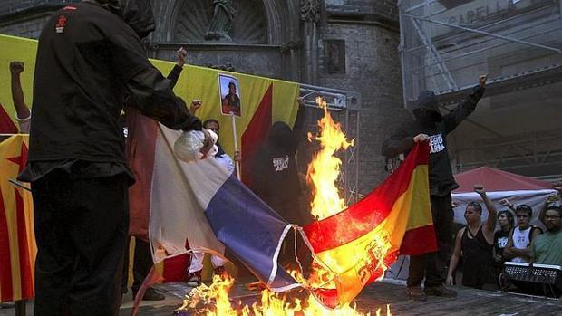 Imagen de 2012 en la que varios manifestantes queman una bandera de España jaleados por la multitud