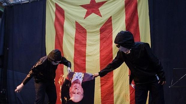 Dos encapuchados preden fuego a una imagen de Don Juan Carlos durante la Diada de 2011