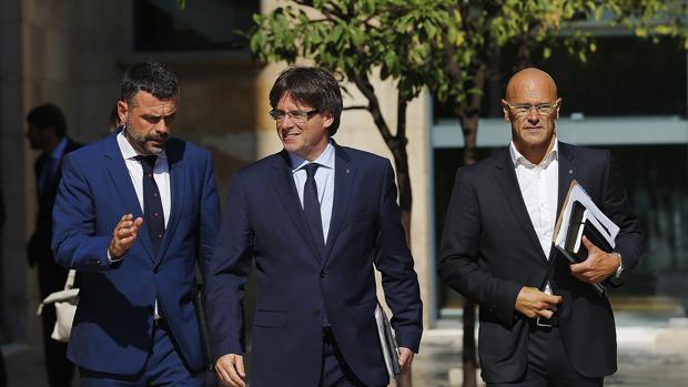 Puigdemont, junto a los consellers Vila y Romeva, ayer antes de la reunión del gobierno catalán