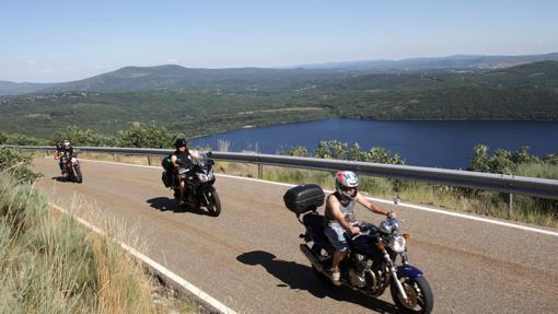 Unos moteros transcurren por la ruta dejando a sus espaldas el lago Sanabria