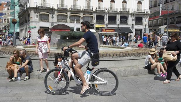 Un ciclista transita por el centro de Madrid con un BiciMad