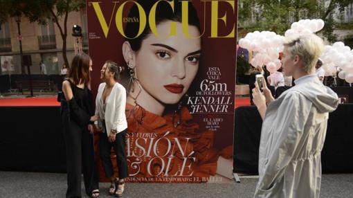 Dos chicas posan frente a una de las portadas de la revista Vogue