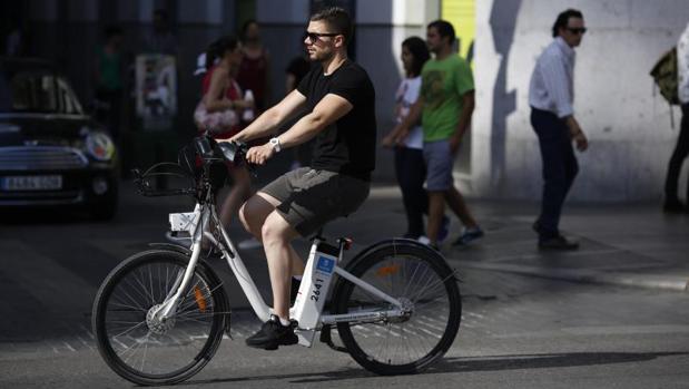 Un usuario del sistema de bici eléctrica, BiciMad, circula por el centro de Madrid