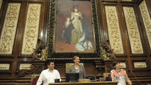 Ada Colau y dos de sus concejales, en el salón de plenos frente a un retrato de la Reina Regente