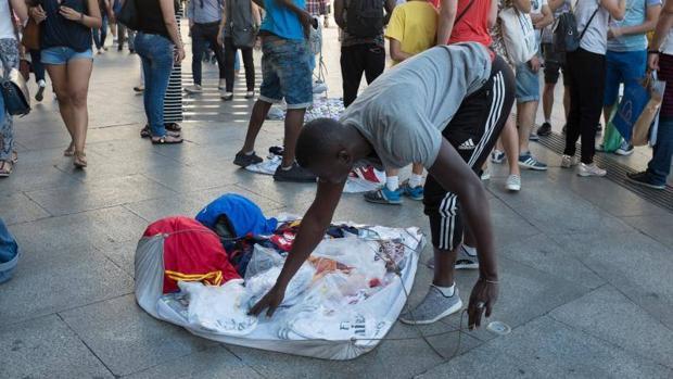 Un mantero recogiendo su mercancía en Madrid