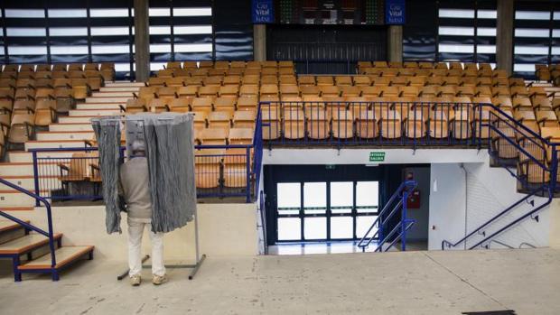 Un hombre elige la papeleta el colegio electoral habiltado en el polideportivo Mendizorrotza de Vitoria