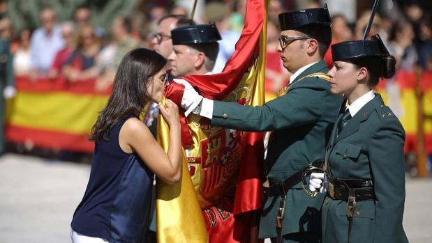 Una mujer besa la Enseña Nacional durante la jura de bandera