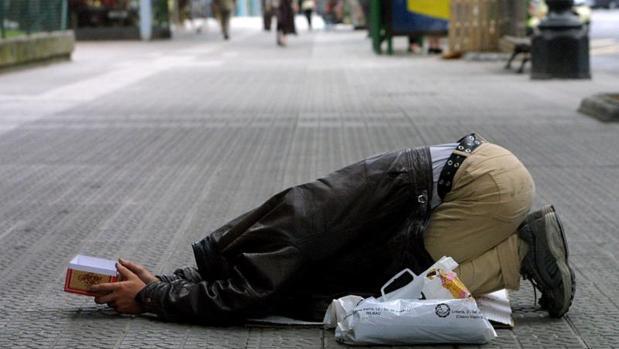 Un mendigo pide limosna ocultando su rostro