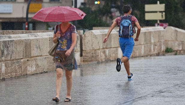 Una mujer se protege de la lluvia en Valencia