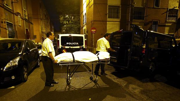 Los servicios funerarios trasladan el cadáver de la víctima, anoche, en Puente de Vallecas