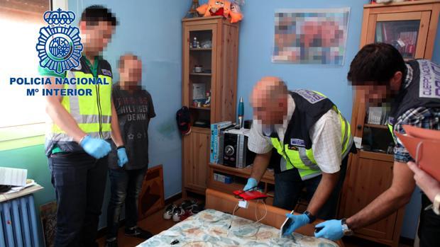 El imputado (segundo por la izquierda), durante el registro realizado por la Policía en su vivienda