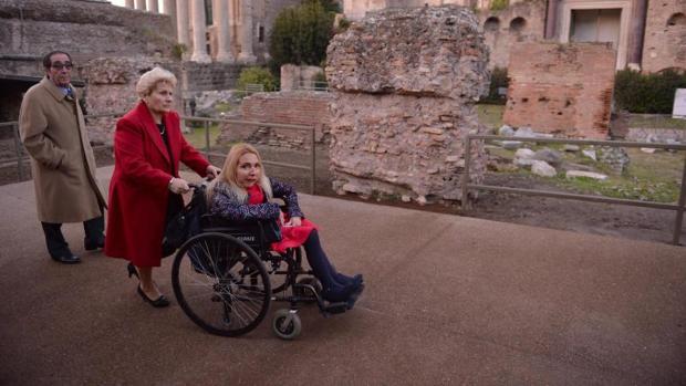 Una turista visita en silla de ruedas restos del patrimonio histórico de una ciudad