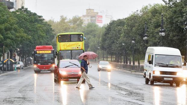 Un hombre se protege de la lluvia en el centro de Valencia