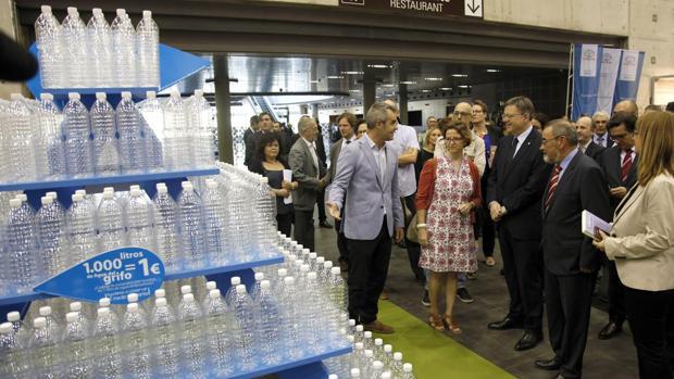 Puig con directivos de Aguas de Valencia y público, junto a la escultura hecha con mil botellas de agua