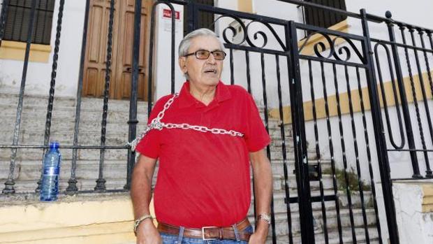 Francisco Gómez, encadenado hoy en la verja exterior de la sede local socialista de Mérida