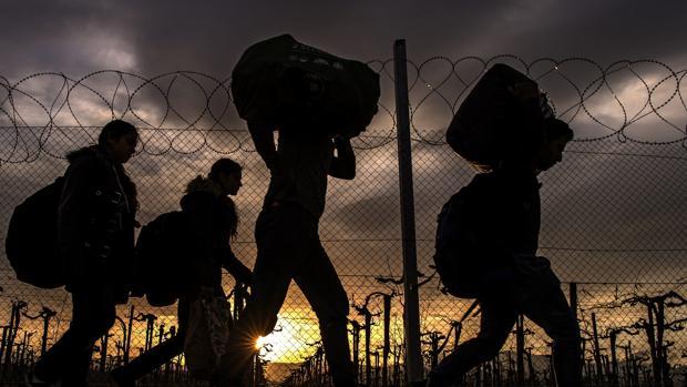 Varias personas cargan con sus enseres en el campo de refugiados de Gevgelija, Macedonia