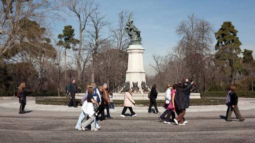 Varios paseantes pasan por delante de la estatua del Ángel Caído