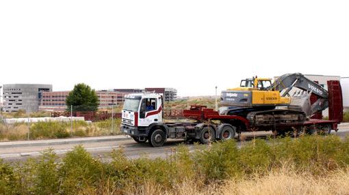Un camión transporta una excavadora, en las inmediaciones del hospital