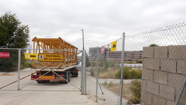 Un camión entra en las obras del hospital cargado con una grúa