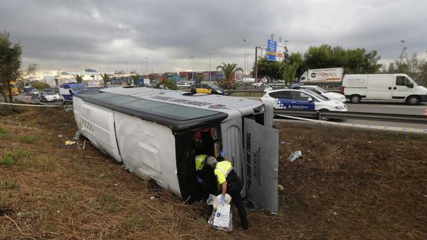 Unos operarios inspeccionan un autobús siniestrado en Barcelona