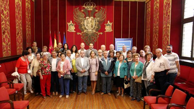 La alcaldesa de Toledo, Milagros Tolón, y el concejal de Servicios Sociales, Javier Mateo, con decenas de personas mayores en la sala capitular del Ayuntamiento