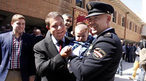 Emiliano García-Page saluda a un bebé en brazos de un policía