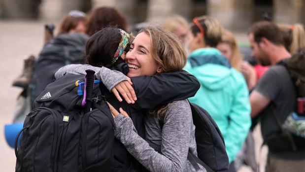 Dos peregrinas se abrazan tras culminar el Camino de Santiago en la plaza del Obradoiro