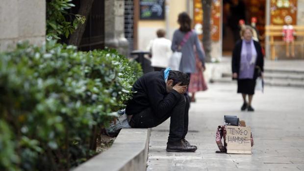 Un hombre pide dinero en las calles de Valencia