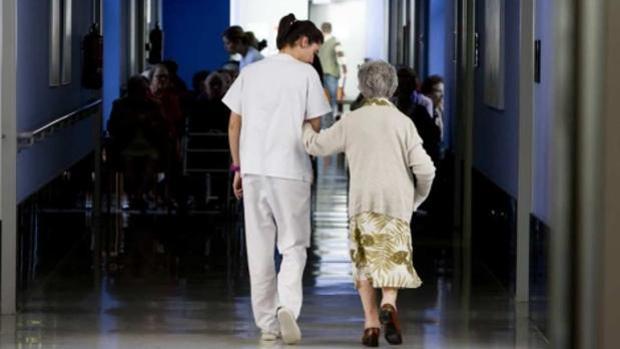 Una anciana acompañada de una trabajadora en una residencia