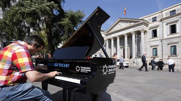 Un músico ofrece un improvisado concierto a las puertas del Congreso