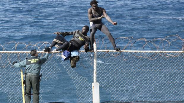 Un guardia civil intenta evitar que dos inmigrantes ilegales salten la valla en Ceuta para entrar en España