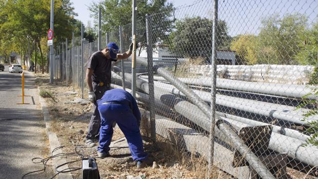 Dos operarios arreglan el vallado después del robo