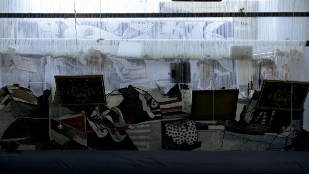 Unos trabajadores afanados en la elaboración de un tapiz