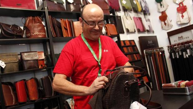 Un artesano sujeta una mochila de cuero