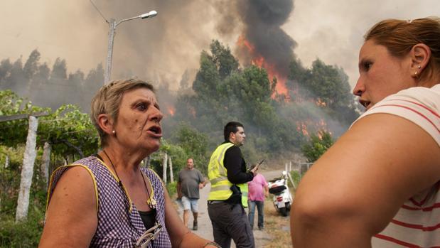 Dos vecinas de Arbo (Pontevedra) conversan durante un incendio forestal en la localidad