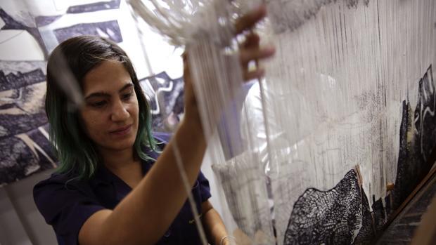 Tania Fernández trabajando en un tapiz artesanal