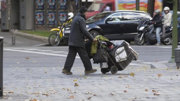 Un hombre cruza con sus pertenencias por el Paseo de la Castellana