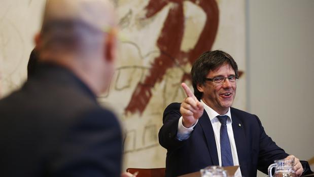 Puigdemont se dirige al consejero de Exteriores, Raül Romeva, duranta una reunión del gobierno catalán