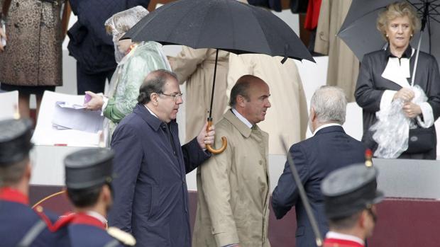 Herrera De Guindos compartieron ayer paraguas en los minutos previos al desfile de las Fuerzas Armadas