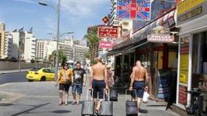 Turistas británicos pasean por una calle comercial de Benidorm